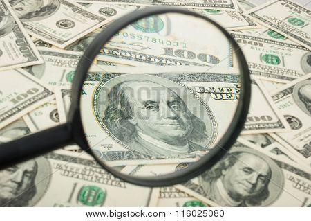 Hundred dollar banknotes under magnifying glass
