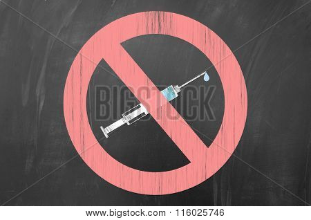 Say no to drugs concept using forbidden symbol and a syringe draw on blackboard.