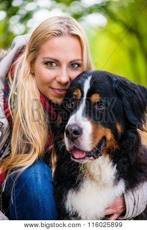 Woman cuddling with Bernese mountain dog in autumn park with colorful foliage, close up shot on head