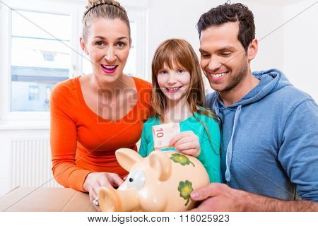 Family saving money by moving house putting bank note in piggybank