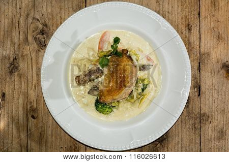 Guinea fowl breast, mustard sauce and mixed vegetables plate from above