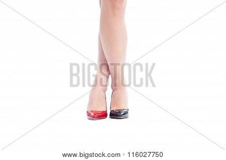Woman Legs Crosses With Different Color Shoes.
