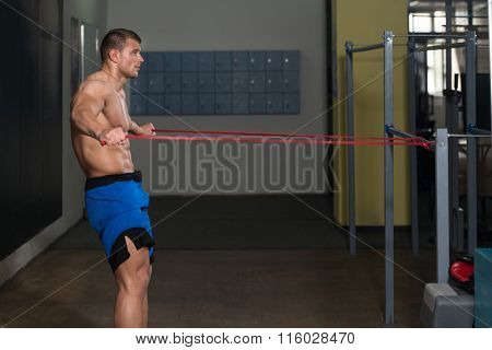 Handsome Guy Working Out With Rubber Indoors