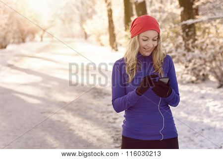 Woman Checking Her Mobile On A Winter Walk