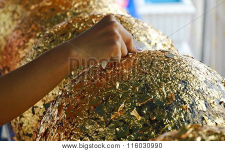 Buddhism put gold leaf on round stone in temple