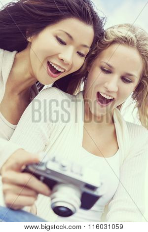 Instagram filter style photograph of two young women girls, one Asian Chinese, one blond, laughing looking at photographs on digital camera