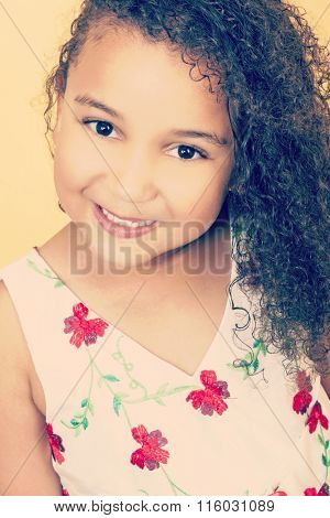 Instagram style filter photograph of a beautiful young mixed race African American girl smiling and looking happy