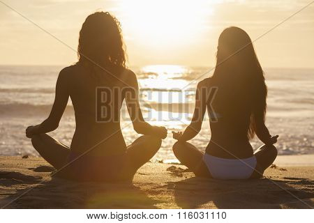 Relaxed sexy young brunette women or girls wearing bikini sitting on a deserted tropical beach at sunset or sunrise