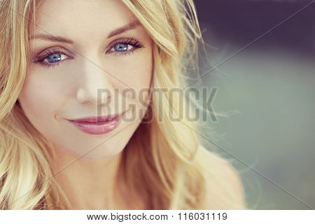 Instagram style portrait of naturally beautiful woman in her twenties with blond hair and blue eyes, shot outside in natural sunlight