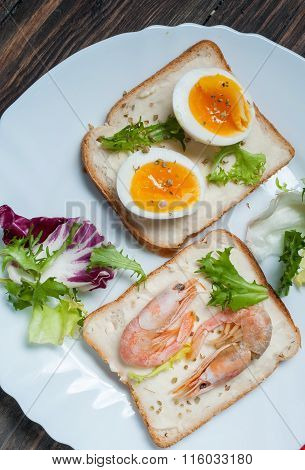 Sandwiches with shrimp, egg, basil, salad, bread on wood background. Delicious cold snacks. Vegetari