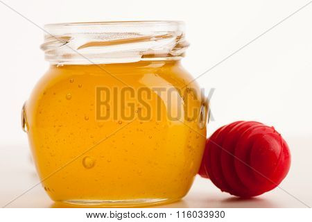 Glass Jar Filled With Sweet Sticky Golden Honey And Red Stick.