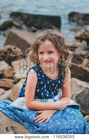 cute curly happy child girl relaxing on stone beach wrapped in cozy quilt blanket.