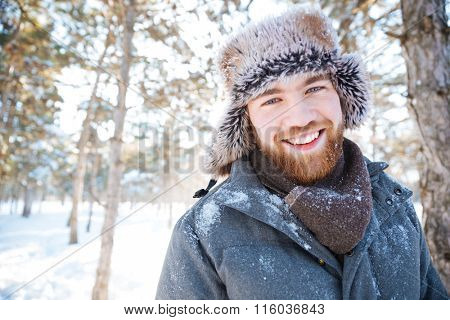 Happy young man looking at camera in winter ark