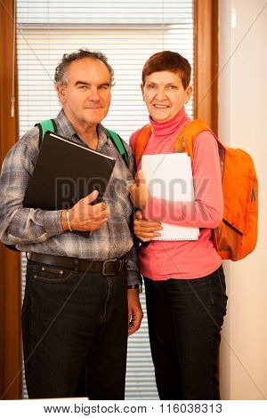Older Couple Representing Lifelong Learning. Couple With School Bags Smiling As A Gesture Of Happine