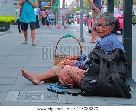 Thai woman beggar sitting on the sidewalk