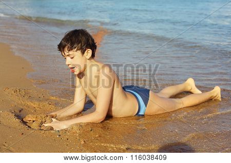 Boy On The Beach Take Sun Bathing Play With Sand