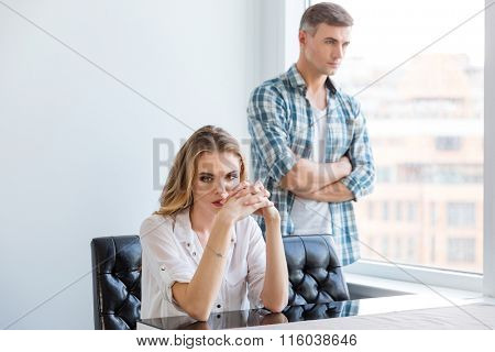 Unhappy couple ignoring each other after argument at home