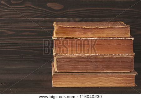 Stack Of Old Books On Dark Wooden Background