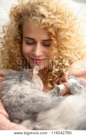Young woman and cat in the room, closeup