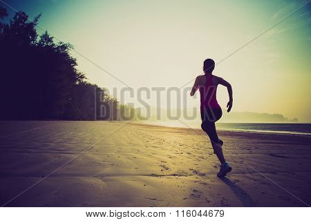 young fitness woman runner running at sunrise beach
