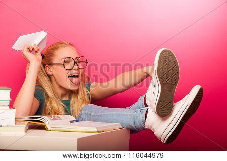 Playful, Naughty Schoolgirl With Big Eyeglasses Throwing Paper Aeroplane Sitting On Floor Behind The