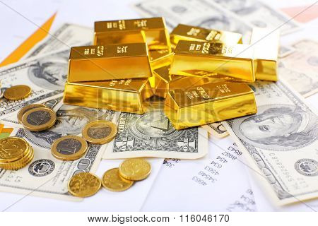 Gold bars with euro coins on dollar banknotes