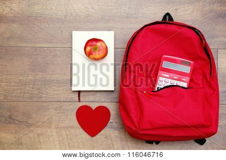 School set with backpack, heart, apple and book on wooden background