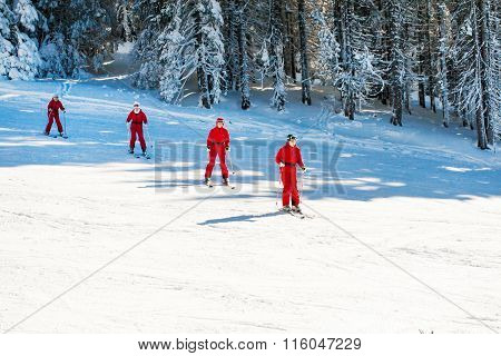 Women in vibrant red jackets skiing at the slope