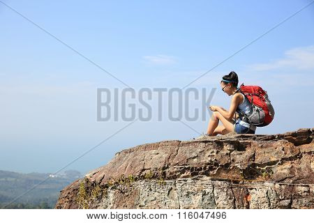 young woman hiker use cellphone  sit on mountian peak