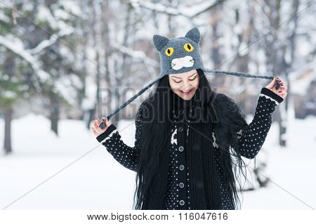 Happy young woman with funny cat hat in park in winter
