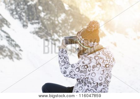 Woman with smartphone in a moutains and taking a photo. Natural light and sun light. Moutains