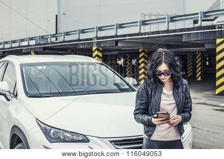 Beautiful Sexy Female Model In Leather Clothes With A White Car And A Smartphone