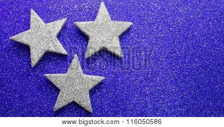 Three Large Stars On Bright Red Glittery Illuminated Background