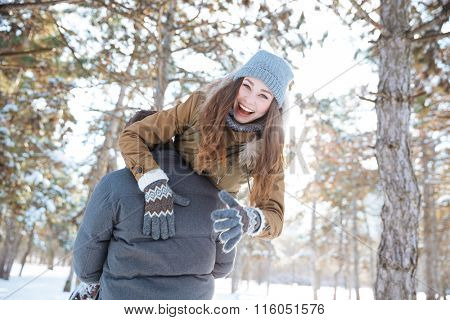 Man carrying happy woman on his shoulders in winter park