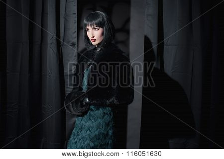 Dark Eerie Witch Fashion Woman Holding Sleeve. Standing In Room With Black Curtains.