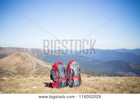 Red backpack standing on top of the mountain.