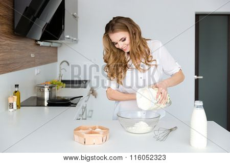 Happy pretty young woman in white shirt standing and cooking on the kitchen