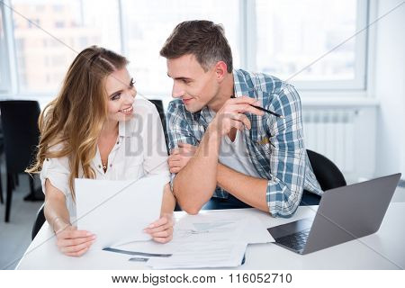 Cheerful man and woman working and flirting on business meeting