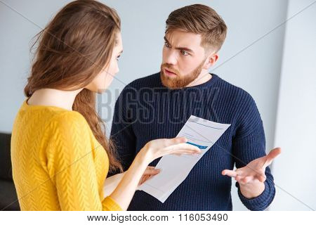 Portrait of a young couple discussing about domestic bills at home