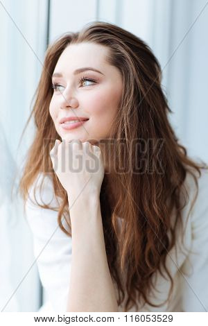 Portrait of beautiful happy young woman with long hair looking at the window