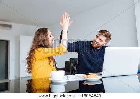 Cheerful couple giving five sign with palms at home