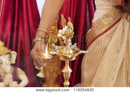 Woman lighting up the metal diya. Traditional Indian Hindus religious ceremony. Focus on the oil lamp. India special rituals events.
