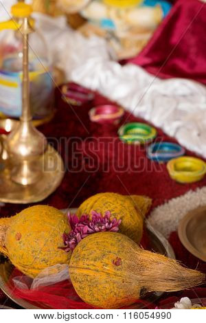 Traditional Indian Hindu religious praying items in ear piercing ceremony for children. Focus on the coconuts.