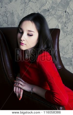 upset teenage girl sitting in the chair