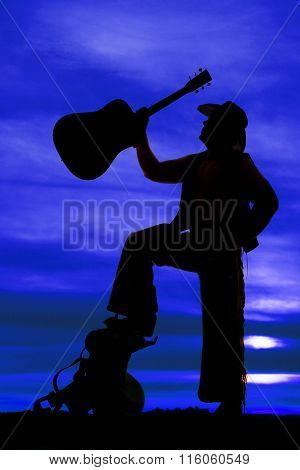 Silhouette Of Cowboy Foot On Saddle Guitar Up