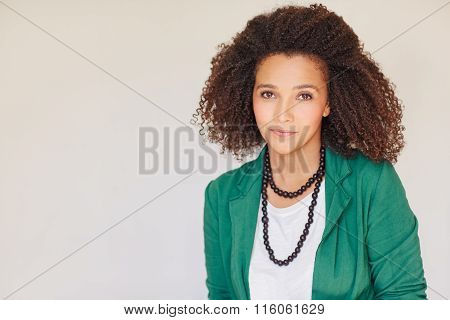 Mixed race businesswon with curly afro in green jacket