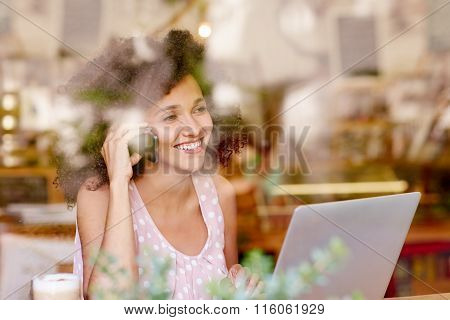 Woman on the phone smiling while in a coffee shop