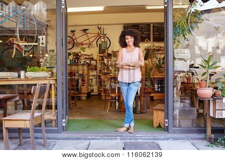 Woman standing happily in the entrance of her coffee shop