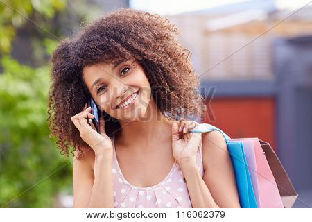 Woman holding shopping bags and listening to her phone