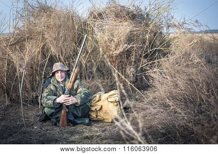 Hunter man with shotgun and backpack having a rest in rural field during hunt season